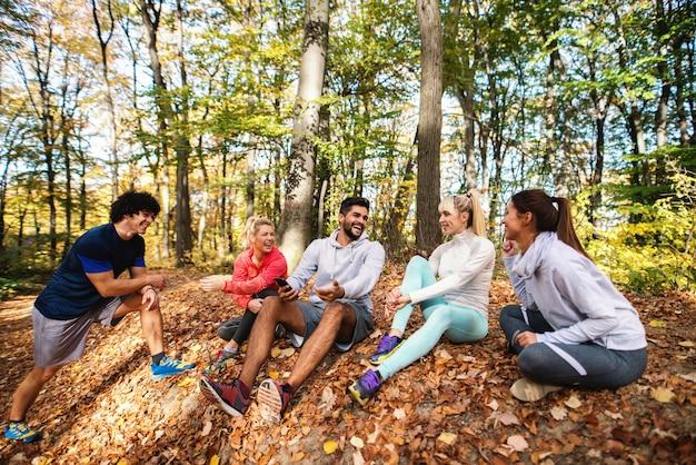 Feliz pequeño grupo de amigos sentados en el suelo en el bosque y descansando de la carrera. otoño.
