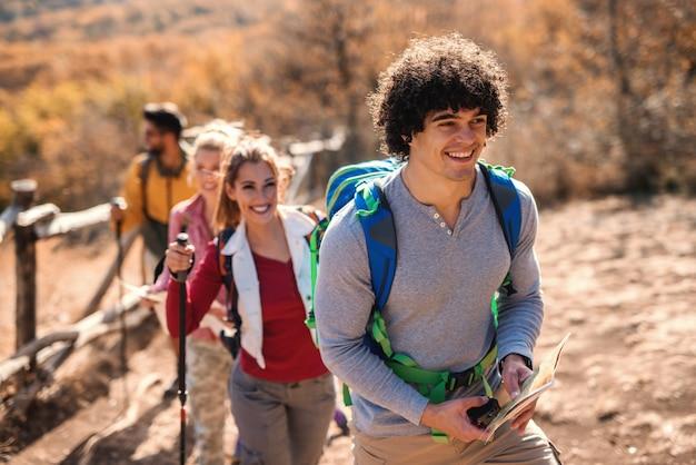 Feliz pequeño grupo de excursionistas caminando en la fila en el otoño. enfoque selectivo en el hombre en primer plano.