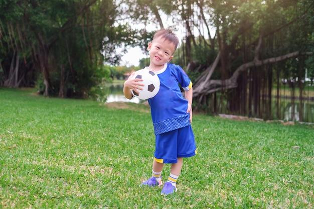 Feliz pequeño jugador de fútbol en uniforme de fútbol está sosteniendo el balón de fútbol