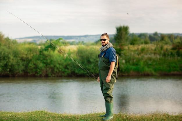 Feliz pescador con traje especial y caña de pescar cerca del río