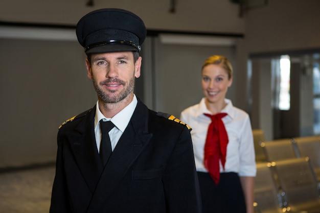 Feliz piloto y azafata de pie en la terminal del aeropuerto