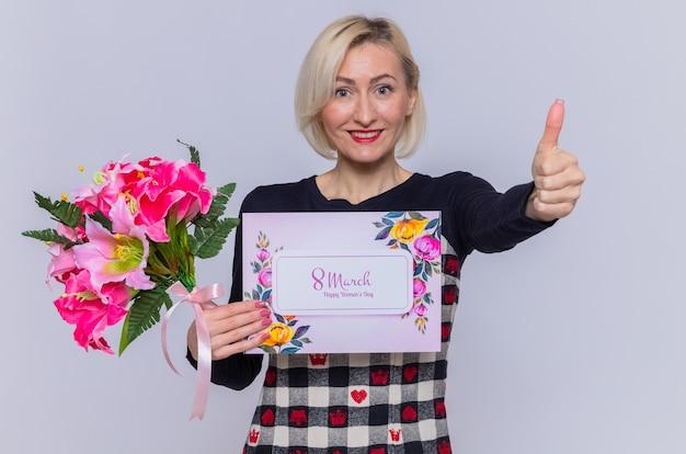 Feliz y positiva joven sosteniendo una tarjeta de felicitación y un ramo de flores