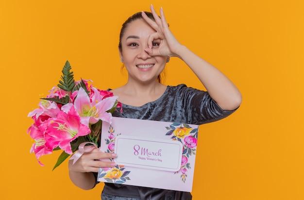 Feliz y positiva mujer asiática madre sosteniendo un ramo de flores y una tarjeta de felicitación celebrando el día internacional de la mujer de marzo mirando a través de los dedos haciendo el signo de ok