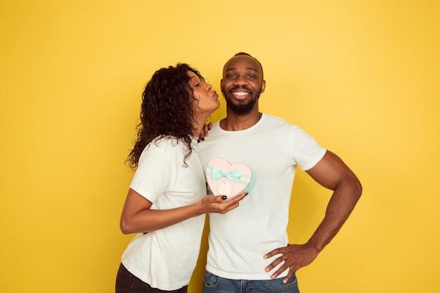 Feliz de recibir un regalo. celebración del día de san valentín, feliz pareja afroamericana aislada sobre fondo amarillo de estudio. concepto de emociones humanas, expresión facial, amor, relaciones, vacaciones románticas.