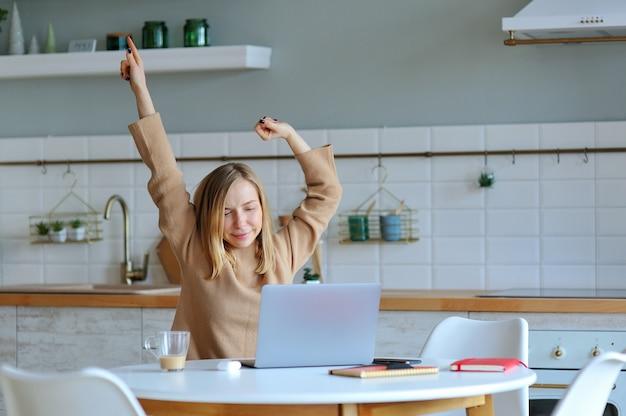 Feliz relajada mujer joven sentada en su cocina con una computadora portátil frente a ella estirando los brazos sobre su cabeza y mirando por la ventana con una sonrisa