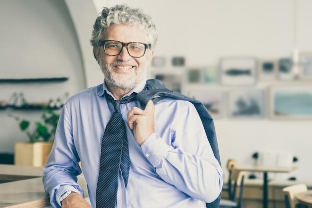 Feliz relajado hombre de negocios maduro de pie en la cafetería de la oficina, apoyado en el mostrador, sosteniendo la chaqueta sobre el hombro