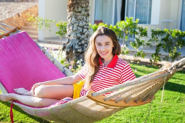 Feliz relajado joven tumbado en una hamaca en vestido casual de verano