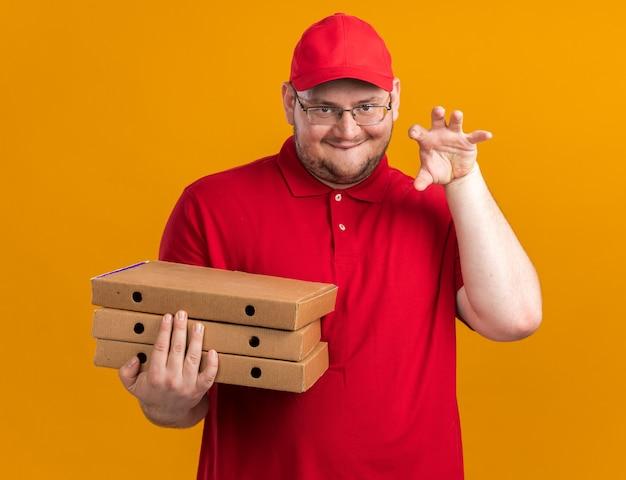 Feliz repartidor joven con sobrepeso en gafas ópticas sosteniendo cajas de pizza y gesticulando la pata de tigre aislado en la pared naranja con espacio de copia