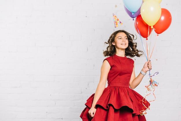 Feliz retrato de una adolescente sosteniendo globos en la mano saltando