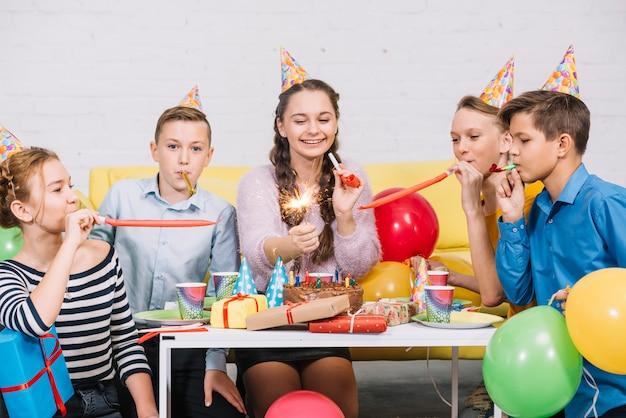 Feliz retrato de una adolescente sosteniendo un petardo en la mano disfrutando en la fiesta de cumpleaños