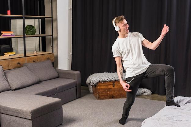 Feliz retrato de un joven tocando una guitarra invisible con auriculares en la cabeza