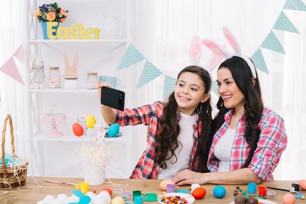 Feliz retrato de madre e hija tomando autorretrato en celular en el día de pascua