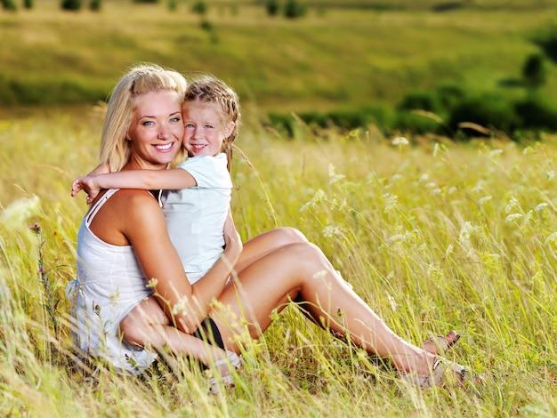 Feliz retrato de la madre y la pequeña hija en la pradera