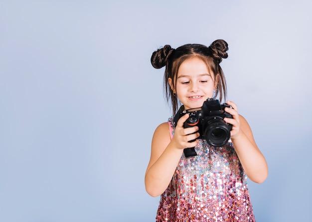 Feliz retrato de una niña mirando a la cámara contra el fondo azul