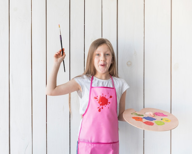Feliz retrato de una niña con pincel y paleta de madera en las manos de pie contra la pared de madera blanca