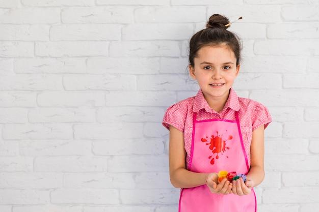 Feliz retrato de una niña sosteniendo botellas de pintura de colores en la mano de pie contra la pared blanca