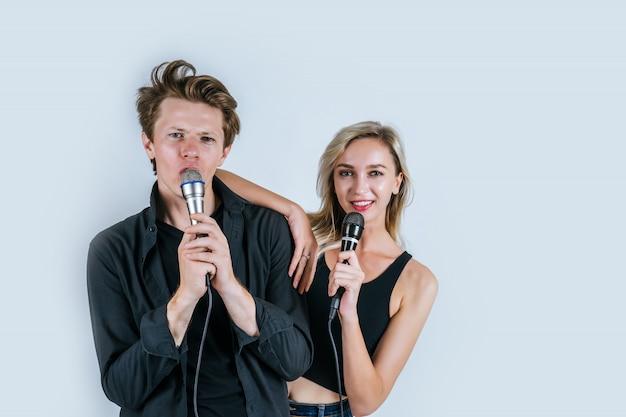 Feliz retrato de pareja con micrófono y canta una canción