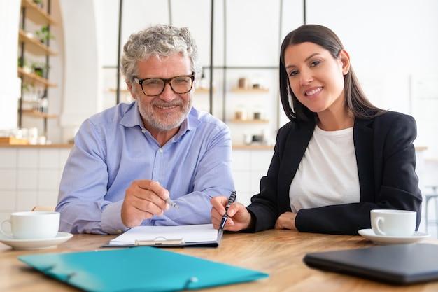 Feliz reunión de agente y cliente con una taza de café en el coworking, sentado a la mesa, revisando documentos,
