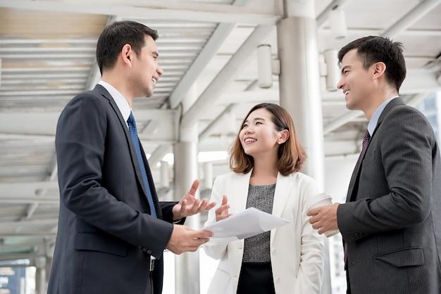 Feliz reunión de asociados de negocios asiáticos fuera de la oficina discutiendo trabajo