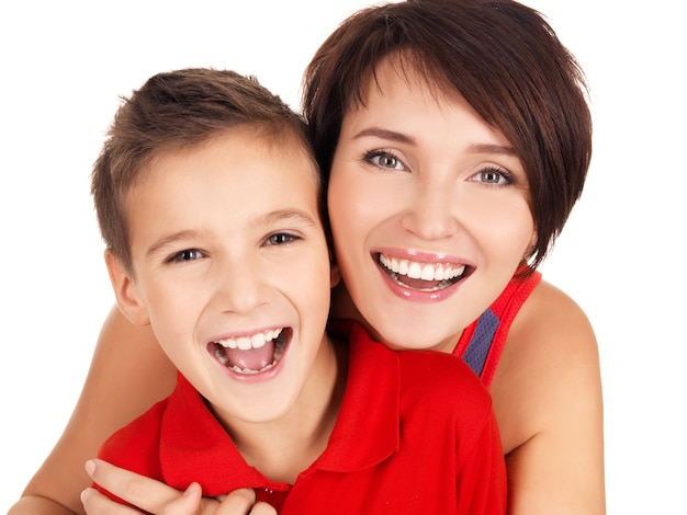 Feliz riendo joven madre con hijo de 8 años sobre fondo blanco.