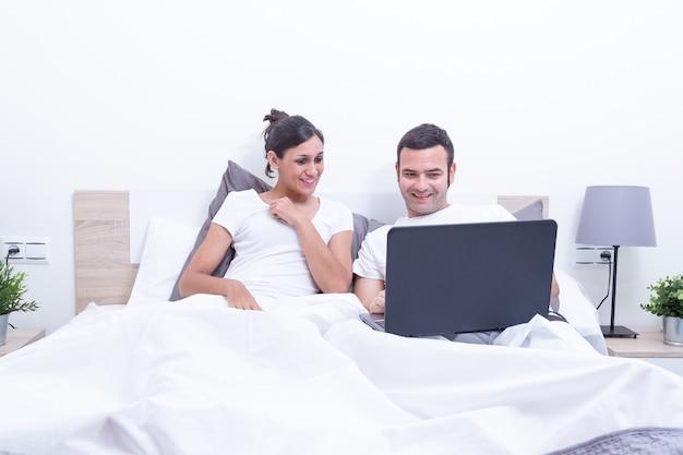Feliz riendo relajado joven pareja usando la computadora portátil en la cama en su casa