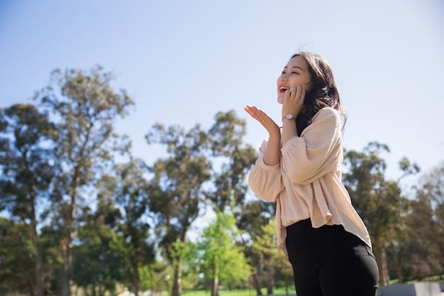 Feliz risa chica asiática totalmente emocionada con charla telefónica