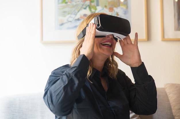 Feliz rubia emocionada disfrutando de la experiencia de realidad virtual en casa