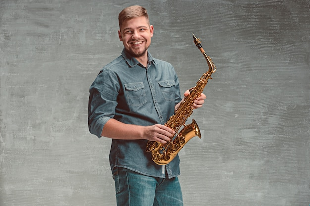 Feliz saxofonista con saxo sobre espacio gris
