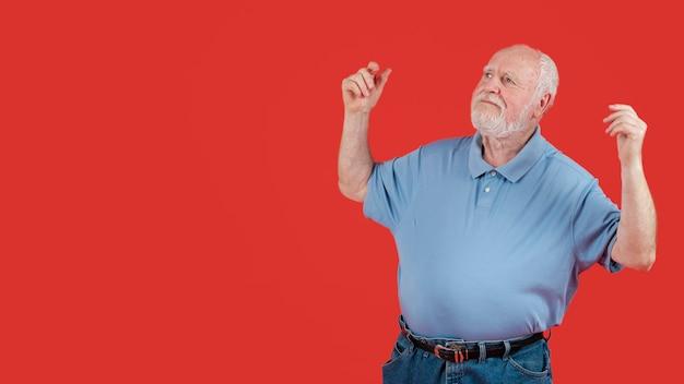 Feliz senior bailando con espacio de copia
