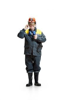Feliz senior barbudo minero masculino de pie a la cámara con el teléfono inteligente en un blanco