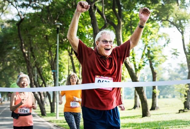 Feliz senior corriendo por la línea de meta