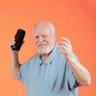 Feliz senior escuchando música en el altavoz