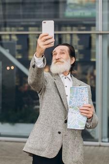 Feliz senior hombre con barba gris un selfie selfie con mapa en el fondo del aeropuerto