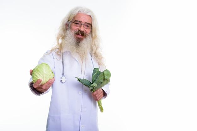 Feliz senior hombre barbudo doctor sonriendo sosteniendo verduras