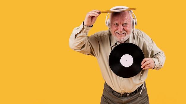Feliz senior jugando con discos de música