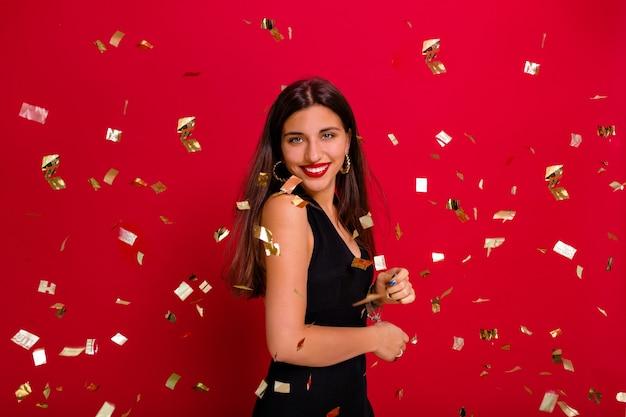 Feliz señorita inspirada celebrando el año nuevo con una sonrisa.