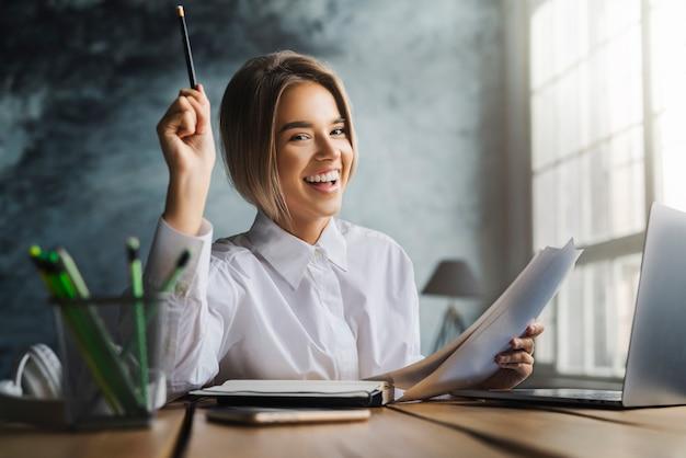 Feliz señorita sentada en el escritorio y estudiando