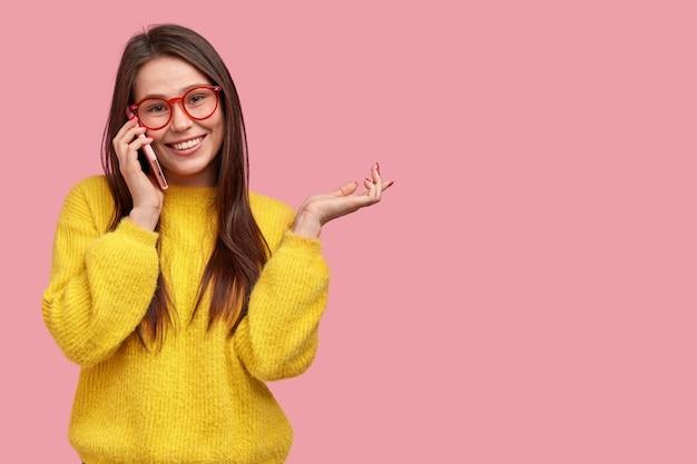 Feliz señorita tiene conversación telefónica con su mejor amiga, gesticula activamente mientras cuenta lo que pasó con ella durante el día