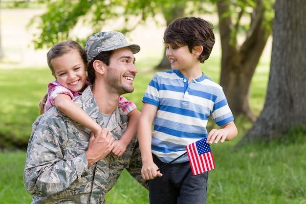 Feliz soldado se reunió con su hijo y su hija en el parque