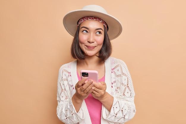 Feliz soñadora joven asiática sostiene un teléfono inteligente moderno en las manos, usa una aplicación celular para chatear en línea, mira hacia otro lado, usa un elegante chal de punto blanco aislado sobre una pared marrón
