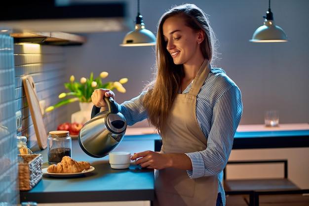 Feliz sonriente ama de casa atractiva joven vertiendo y haciendo té con hervidor eléctrico para el descanso para tomar café por la noche en la moderna cocina estilo loft