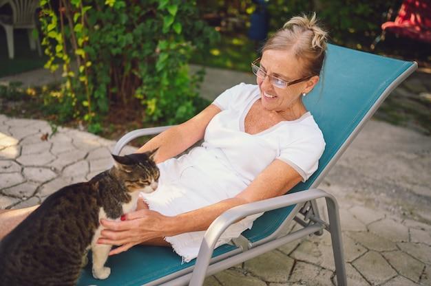 Feliz sonriente anciana en vasos de relax en el jardín de verano al aire libre abrazando gato atigrado doméstico. concepto de mascotas jubilados ancianos y animales