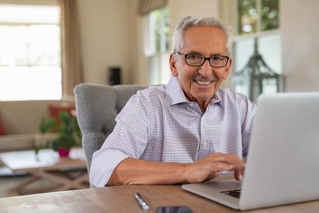 Feliz sonriente anciano con laptop