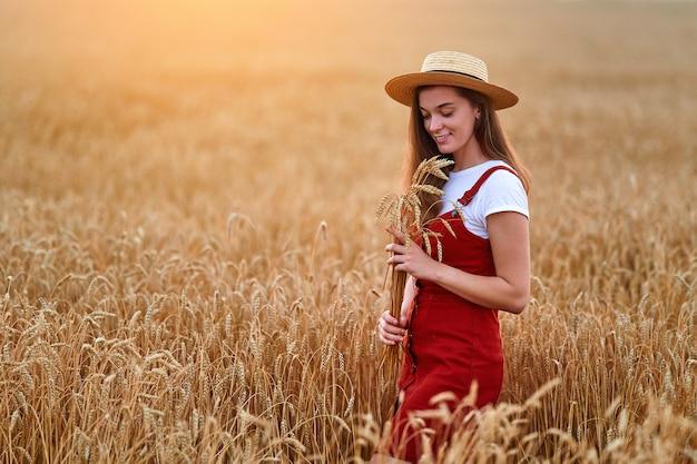 Feliz sonriente atractiva linda mujer joven libre con sombrero de paja y mezclilla en general de pie solo en el campo de trigo amarillo dorado y disfrutando de la hermosa vida del momento de libertad en verano