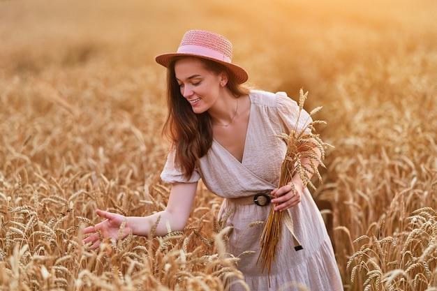 Feliz sonriente atractiva linda mujer joven libre con sombrero y vestido de pie en el campo de trigo amarillo dorado y disfrutando de la serena y hermosa vida del momento en verano