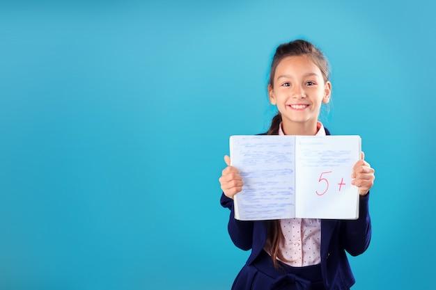 Feliz sonriente colegiala en uniforme sosteniendo y mostrando portátil con excelentes resultados de prueba o examen