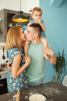 Feliz sonriente familia caucásica en la cocina preparando