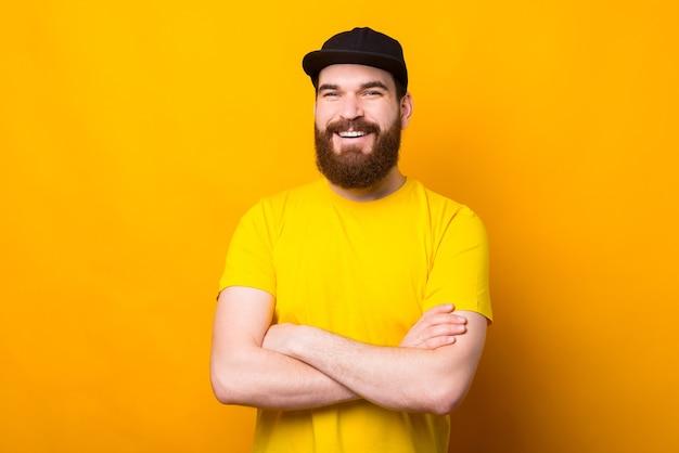 Feliz sonriente hipster barbudo hombre en camisa amarilla de pie con los brazos cruzados.