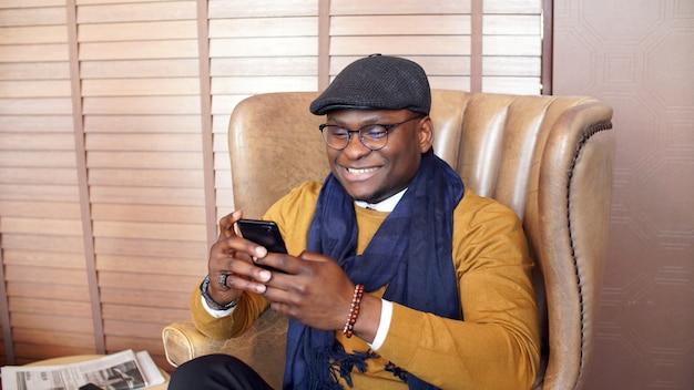 Feliz, sonriente hombre afroamericano sentado en una silla en un elegante restaurante caro, cafetería con un teléfono inteligente, teléfono en mano