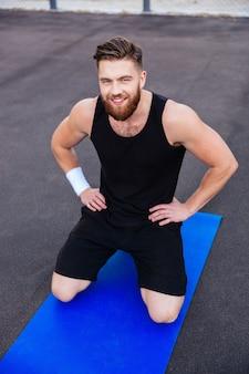 Feliz sonriente hombre de fitness barbudo haciendo ejercicio en la alfombra azul al aire libre